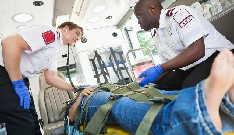 two men diagnosing a patient on the ambulance