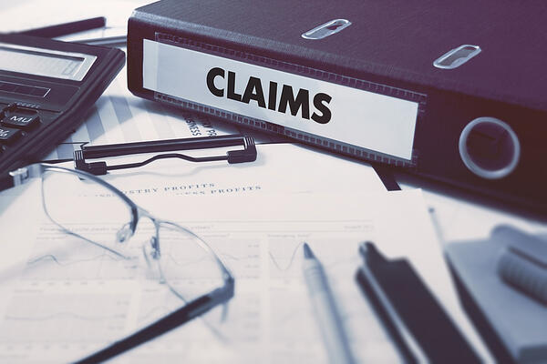a full table of claims document, pen, calculator and glasses