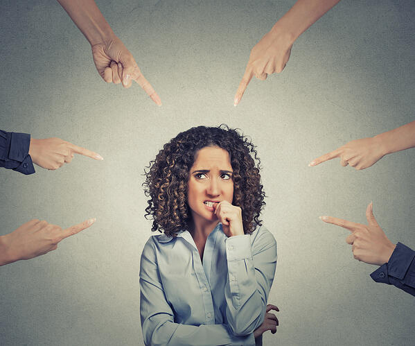 Concept of social accusation of guilty businesswoman many fingers pointing at isolated on grey office wall background. Portrait scared anxious embarrassed woman biting fingernails