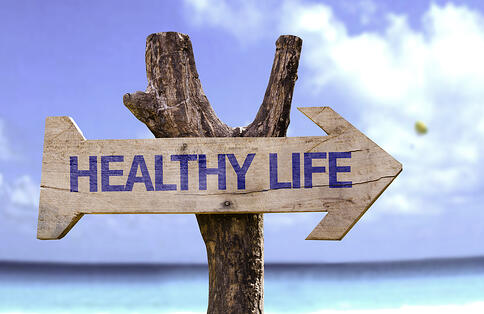 Healthy Life wooden sign with a beach on background