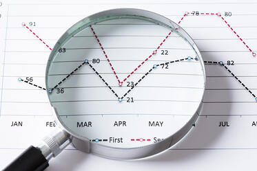 Magnifing glass and documents with analytics data lying on table-1