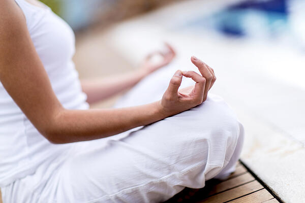 Yoga woman meditating and making a zen symbol with her hand