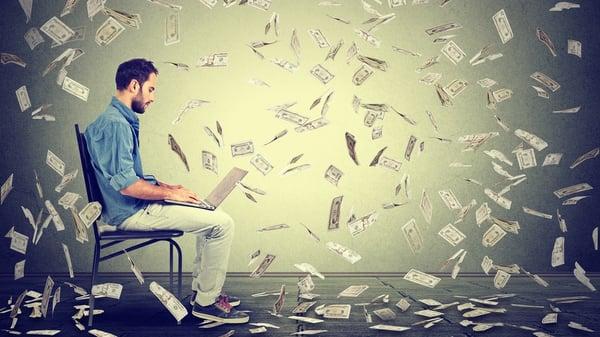 Young man using a laptop building online business making dollar bills cash falling down. Beginner IT entrepreneur under money rain. Success economy concept Cropped