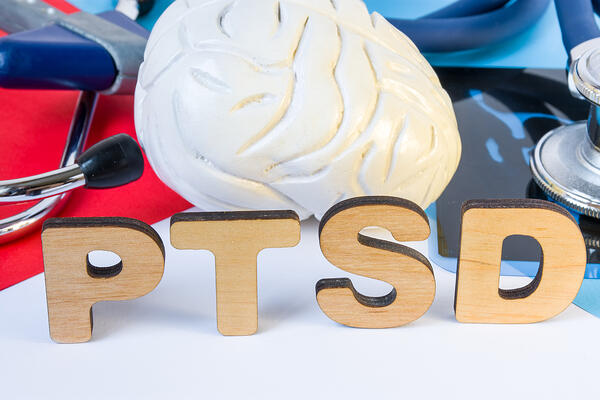 PTSD wooden letters in front of brain model