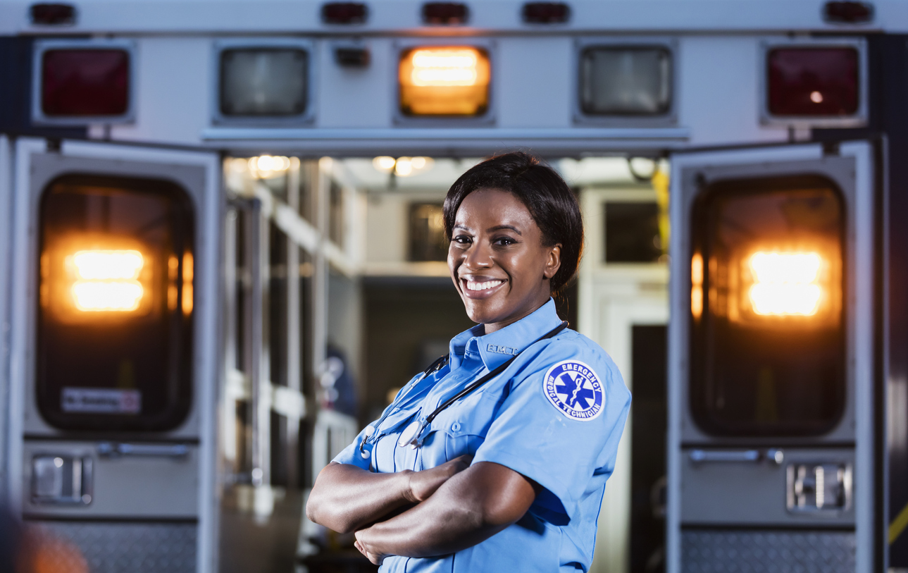 Female EMT standing with arms crossed smiling in front of ambulance