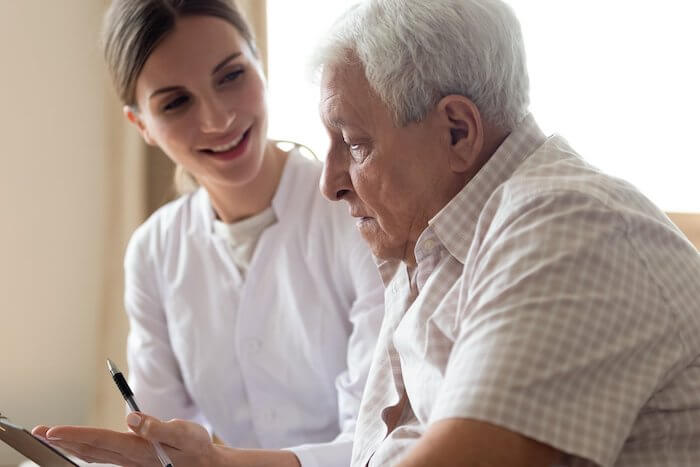 Healthcare worker explaining form to older male patient
